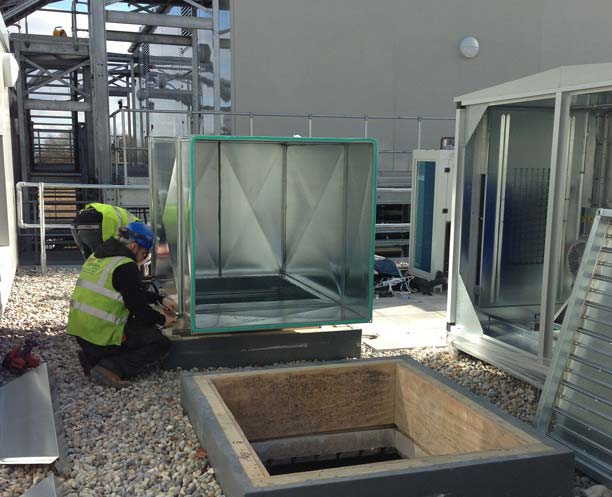 an image showing two Vent Logistics employees working on an outisde ventilation system