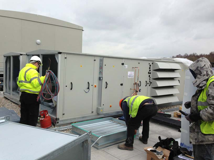 An image showing three Vent Logistics employees installing a Ventilation system outside.