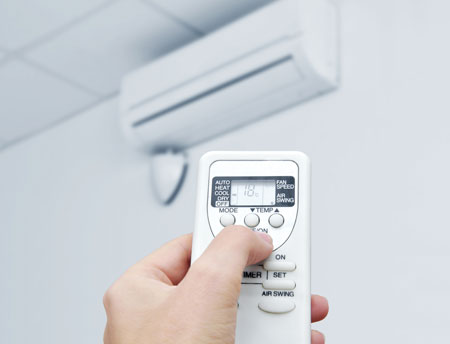 An image showing a white remote control operating a Commercial Air Conditioning system.