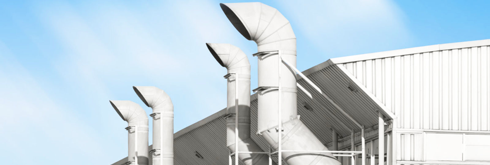 An image showing four air pipes outside on a roof.